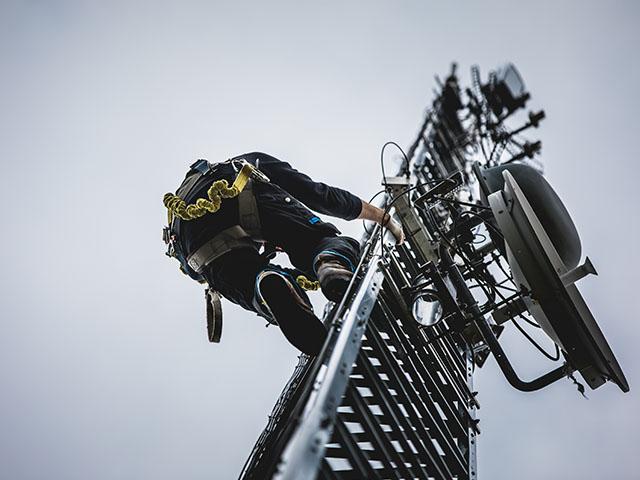 antenna-tele_0003_telecom-worker-climbing-antenna-tower-PEZMGB3